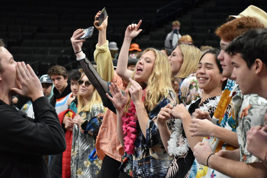 Senior Zoe Kozlowski cheers from the student section as math teacher Bobby Otto leads a cheer.       Otto led the fans in various cheers throughout the match.