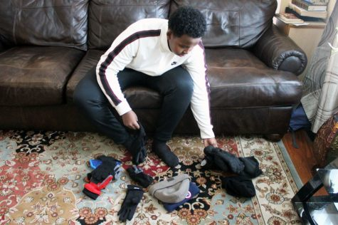 Sophomore Adil Ade organizes hats and gloves to prepare for his next project Nov. 20. His organization Pocket Change Foundation helps the homeless.