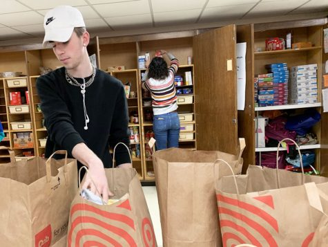 Senior Hayden Haase packs food for donations Dec. 11. The National Honors Society joins the Birdfeeder and Clothing Closet to help the community. As an incentive, all three groups are giving a donut party to the third hour that donates the most items.