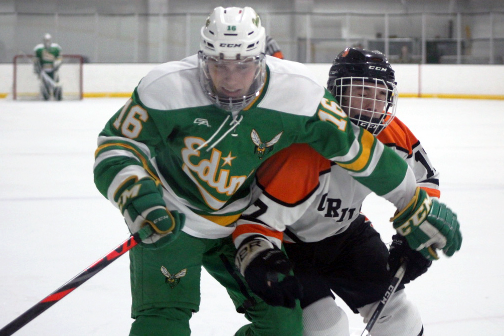 Junior Drew Boyum fights for the puck against Edina's junior Emmett Wurst Dec. 3. Boyum has scored or assisted in at least one goal every game in the first three games of the 2019-2020 season, with a total of four points.
