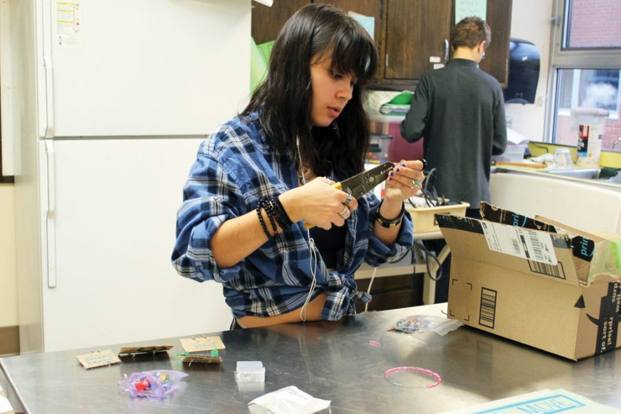 Sophomore Anna Overall makes earrings for her group's small business on Nov. 25. Overall's group 'Jewelry Junkies' makes jewelry from recycled materials and sells their products in school.