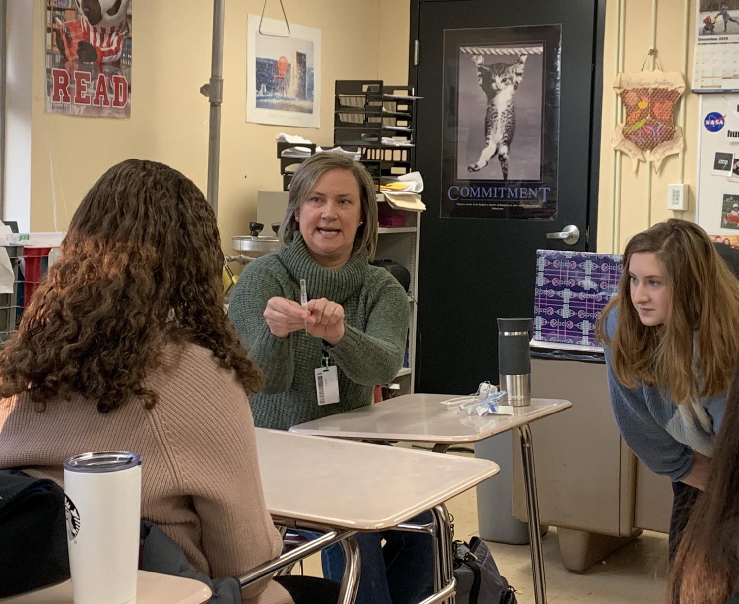 Home care nurse Heather Mcleod describes how to put an IV in to senior Emma Tight. Med club invited Mcleod to speak to students about her profession at the club meeting Dec. 17.