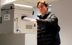 Senior Blake Grant grabs a piece of paper from the student printer Dec. 2 in the At-Large Lab. According to librarian Ellen George, students and teachers now use separate printers.