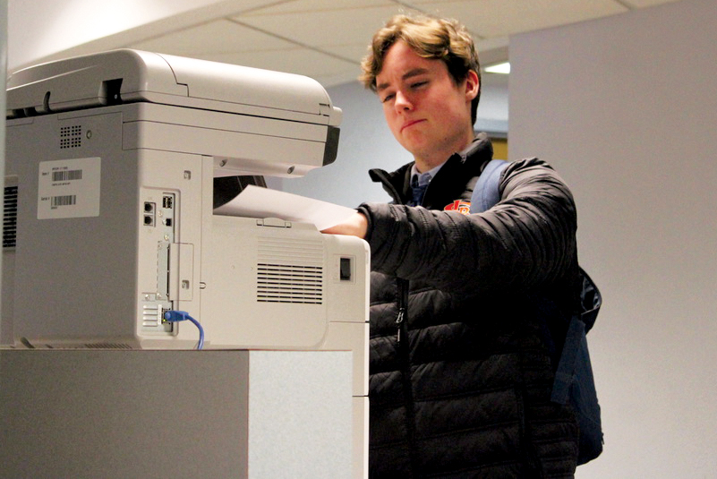 Senior+Blake+Grant+grabs+a+piece+of+paper+from+the+student+printer+Dec.+2+in+the+At-Large+Lab.+According+to+librarian+Ellen+George%2C+students+and+teachers+now+use+separate+printers.
