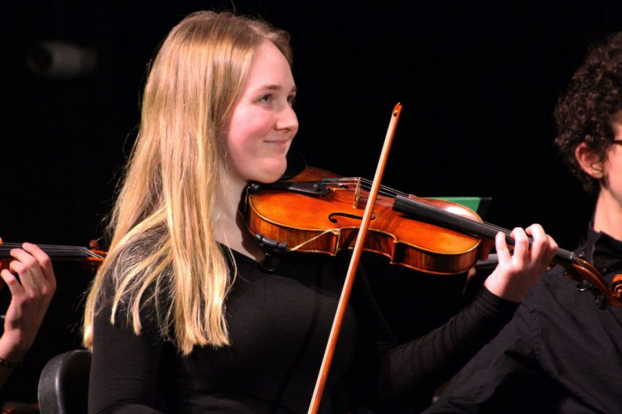 Junior+Iris+Wallestad+smiles+while+playing+the+violin+during+the+orchestra+concert+Dec.+19.+The+orchestra+played+an+array+of+different+music+to+showcase+their+abilities.
