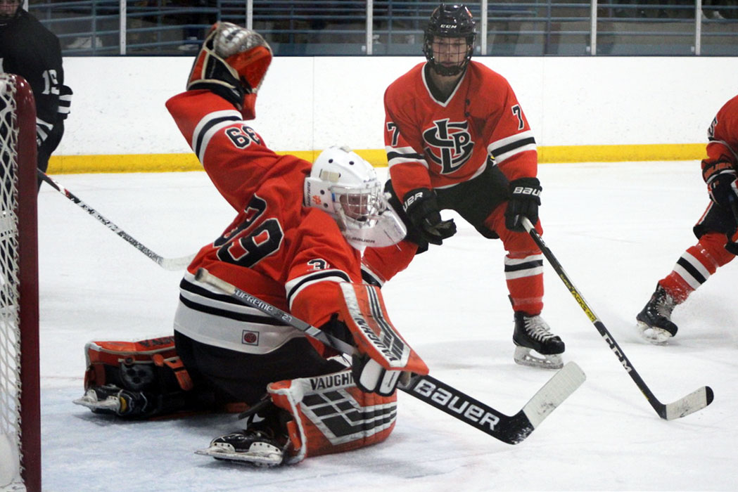 Seniors Will Pinney and Jacob Young work to stop a shot against Minneapolis Dec. 10. Pinney has a save percentage of .887 in the 2019-2020 season, according to the Star Tribune.