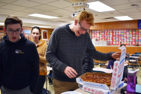 Senior Patrick Djerf smiles as he opens the pizza box during a pizza party in his history class. Djerf won this celebration by being on time 50 days in a row, a challenge that was set between him and his history teacher in October.