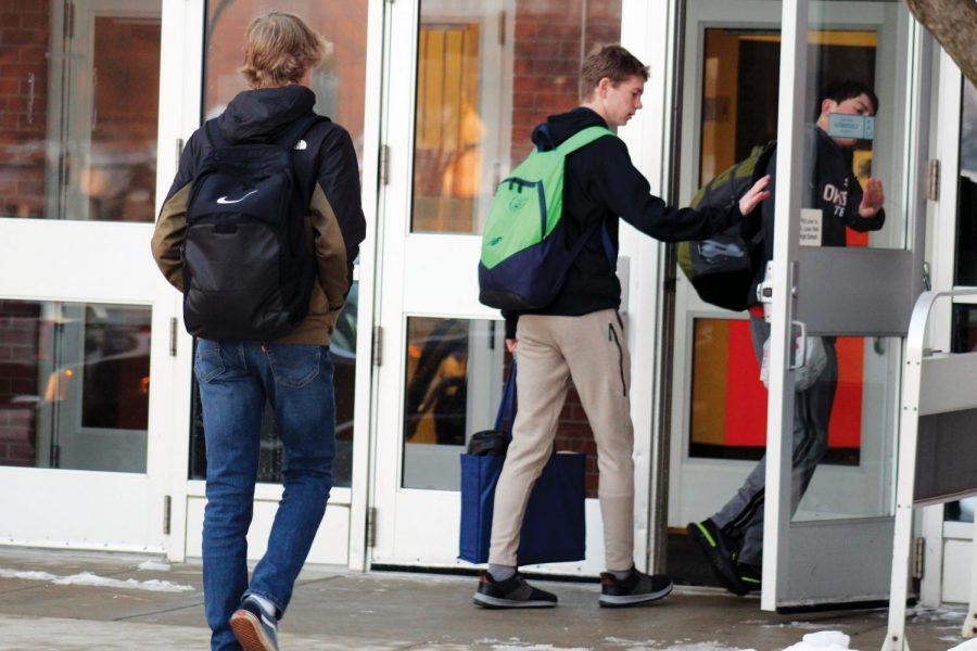 Junior Clayton Horstman-Olson holds the door at the entrance of the school Dec. 20. Winter break for the 2019-2020 school year was Dec. 21 - Jan. 1.