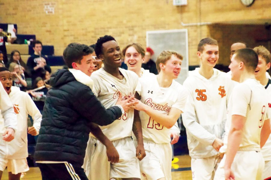 Junior Paris Johnson rejoices with his team after a three point shot to win the game Jan. 30. The final score was 63-61 in favor of Park.