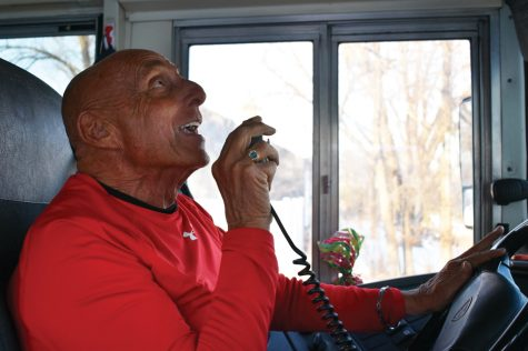 "Bus driver Jay Wolkenbrod sings ""Happy Birthday"" to a student Dec. 20. Wolkenbrod celebrates birthdays and brings gifts, including a balloon and a card, to students."