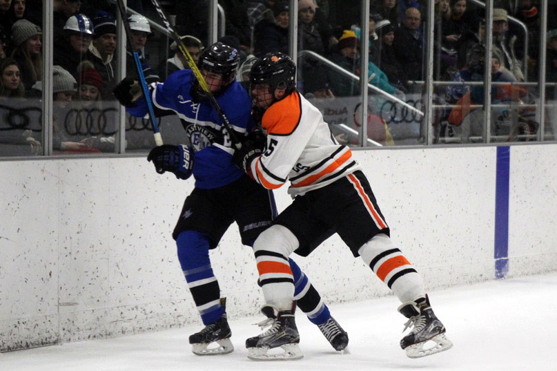 Junior McCabe Dvorak checks Eastview senior Ben Malloy against the boards Jan. 3. Park 3-4 in overtime against Eastview.
