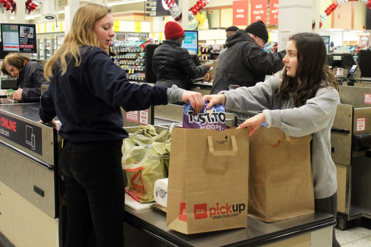 Echowan members and juniors Casey Hunter and Rachel Stein bag a customer's groceries Jan 19 at Cub Foods for an Echowan fundraiser. Echowan will be taking club photos Feb. 13 in the old gym.