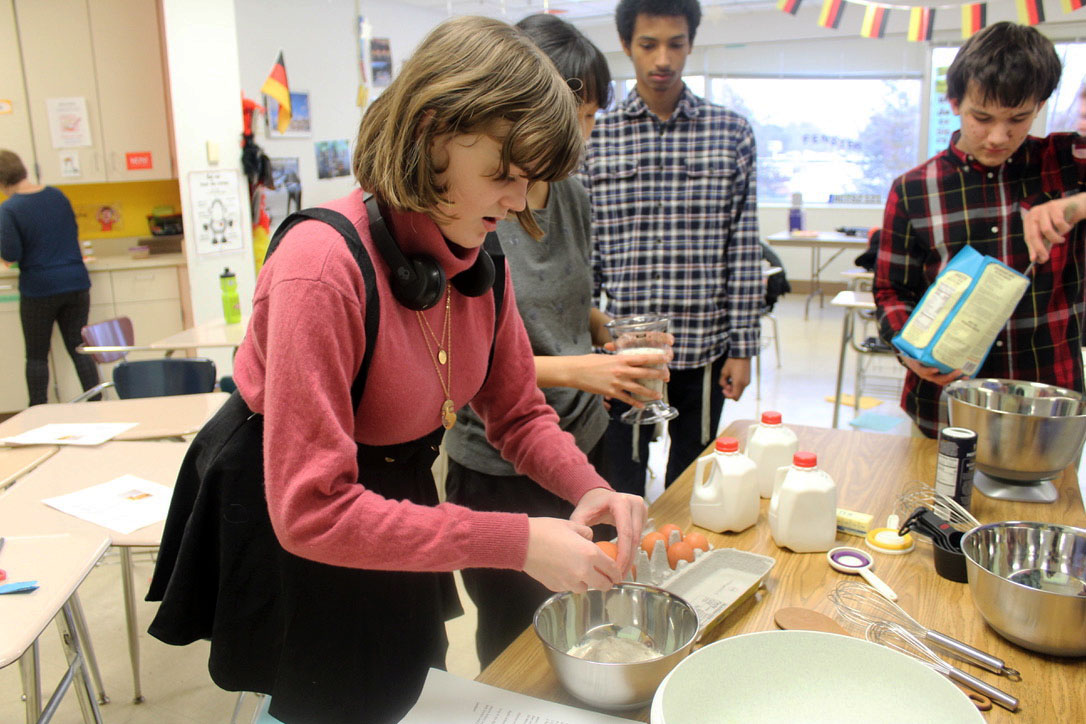 Sophmore Marisa Peck bakes a traditional German pancake in the German club meeting Jan. 13. Juniors Yehoshua Leib Leahy and Thor Anderson help in making the apple pancakes.