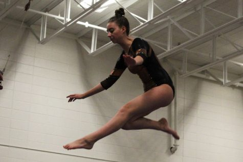 Freshman Ella Wasvick performs her beam routine Jan. 28 at Central Community Center. The gymnastics team lost their meet against Bloomington with a score of 124.8.