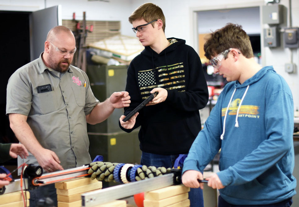 Robotics adviser Trevor Paulson works with junior Nick Perszyk during the team's meeting Feb. 10. According to Paulson, the team does not have a class during school hours to work so it has to stay after school.