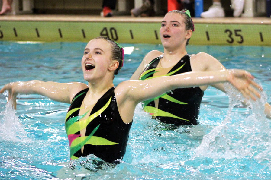 Seniors Ella Hammerstrand and Mia Miller perform a pop-up during Aquafins show Feb. 8. The annual Minnesota Aquafins show consisted of 17 performances from all age groups.