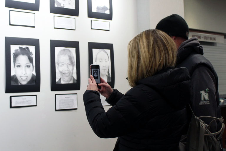 A women takes a picture of student artwork at the gallery in St. Louis Park City Hall. The gallery, which took place Feb. 10, was created to showcase student artwork to the public.