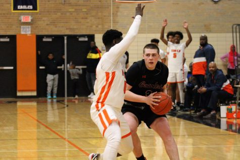 Senior Cole Ewald protects the ball from Cooper defender Feb. 24. The final score of the game was 48-54.