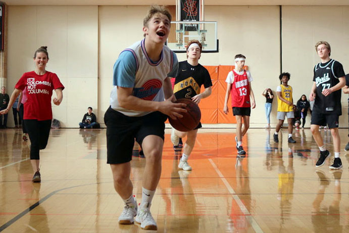 Junior Drew Boyum runs down the court at the annual teacher student basketball game during a pep fest to kick off Sno Daze week. There will be a second pep fest on Feb. 21.