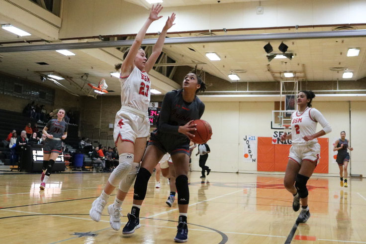 Junior Raegan Alexander takes a shot at the basket at the game against Benilde-St. Margarets Feb. 18. Alexander scored her 1,000th point at the start of the game.