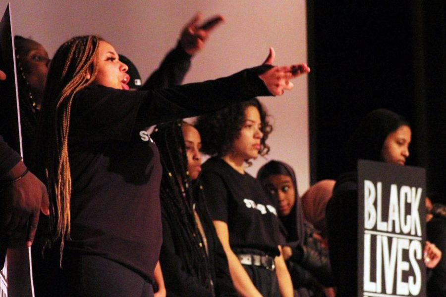 Senior Nevaeh Emerson holds her hands in the likeness of a gun during a poem about police brutality. The poem was written and performed during the Black History Month show by senior Lyric Robinson.