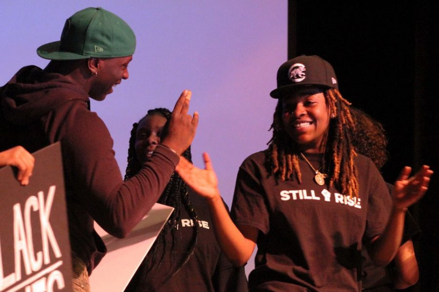 Seniors KyAreia Malone and Tobyous Davenport high five after the sixth hour performance. Following the conclusion of the show, many of the performers danced and took pictures together on the stage.