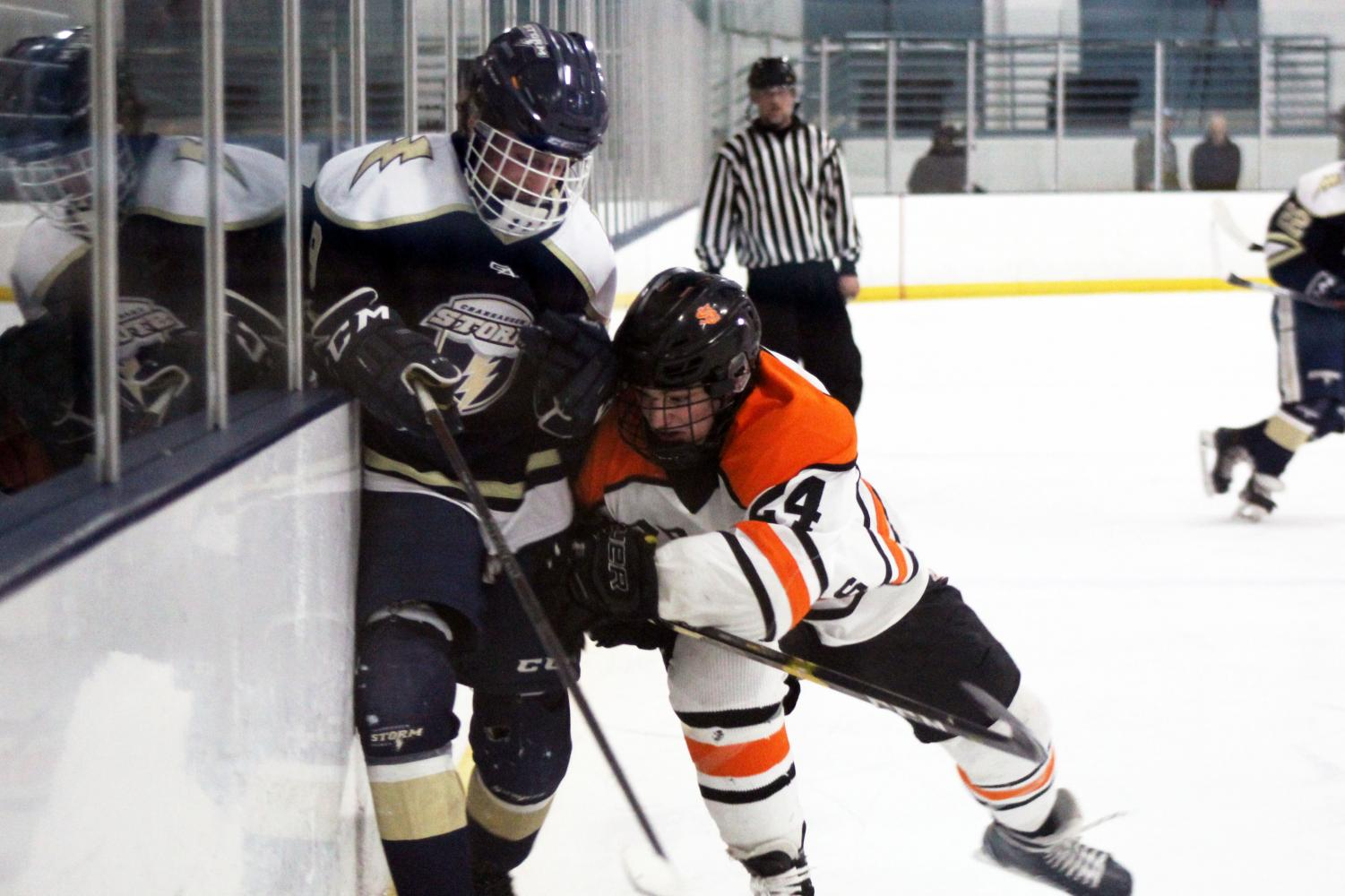 Senior Bobby Doss checks Chanhassen player Parker Thomas into the glass Feb. 6. Park currently holds a winning record of 14-8-0.