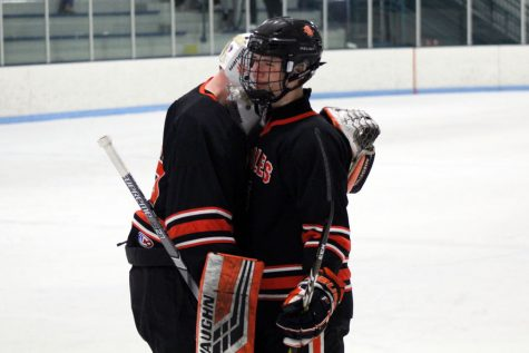 Seniors Jacob Johnson and William Pinney embrace each other following the Feb. 20 Sections loss against Cretin-Durham Hall. The final score of the game was 3-6.