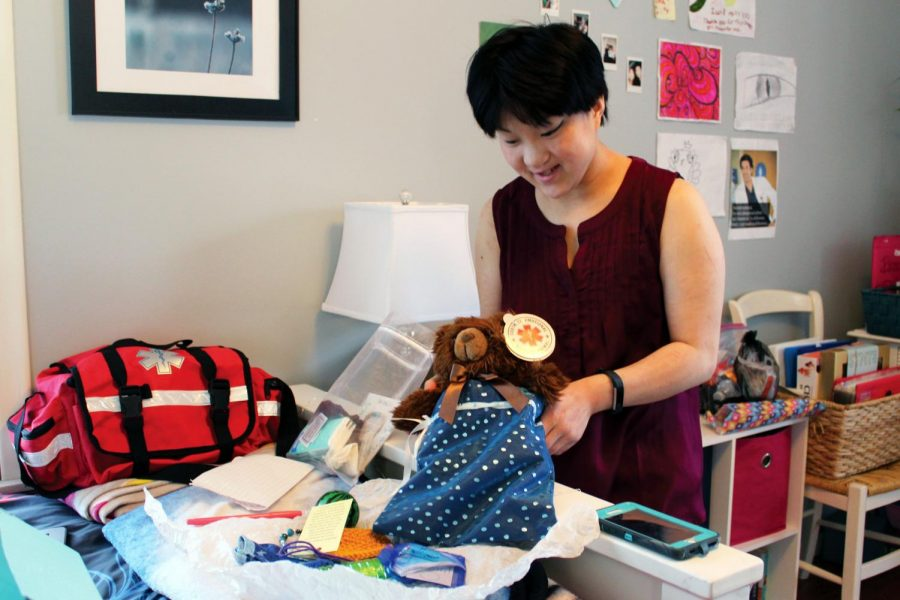 Junior Jae Stanberry packs a weighted aromatherapy teddy bear into a bag for a patient Feb. 20. Stanberry stores supplies and boxes in her room to assemble the packages she makes.