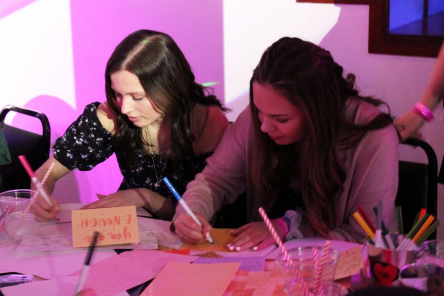 Two Letters of Love Gala attendees write cards to hospitalized children. The goal of the event was to give a card, blanket or bracelet to every child. Letters of Love started at Orono High School last year and has spread to several schools since.
