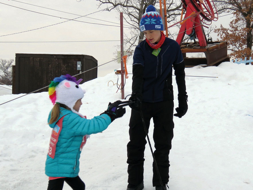 Sophomore Adam Gips helps a girl off the tow rope at the Theodore Wirth Trailhead-Park tubing hill. Gips works at the hill alongside sophomores Tait Myers and Ryan Fitzpatrick.