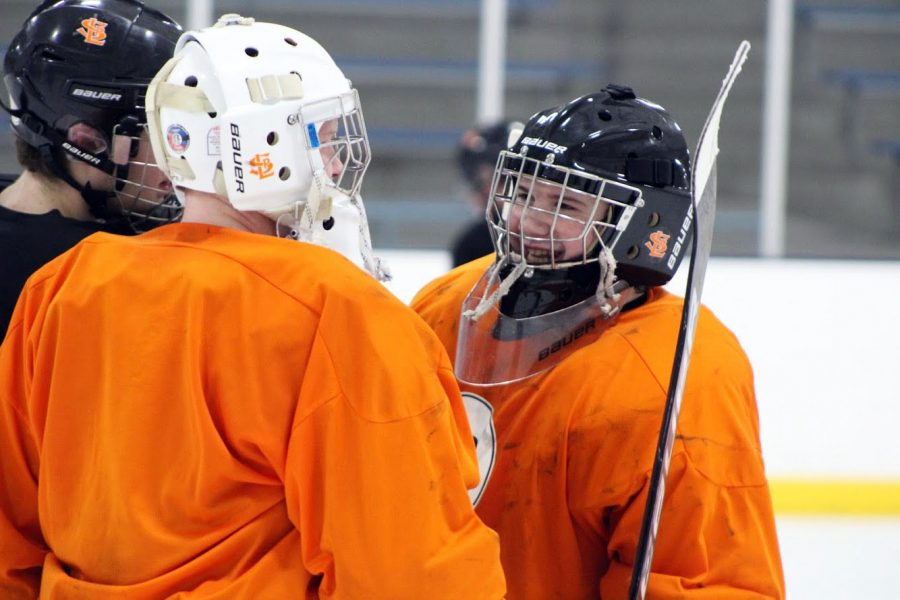 Seniors Flynn Spano and William Pinney talk center ice after practice Jan. 31. Spano and Pinney spent the first portion of practice working on goalie skills.