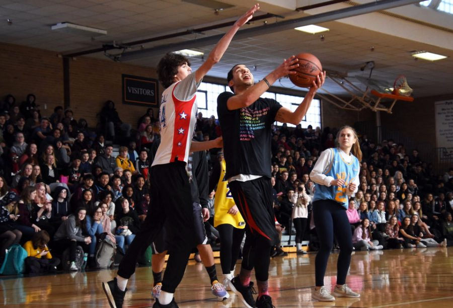 Teacher Alexander Polk attempts a shot while playing the student team during the pep fest Feb. 14. The Sno Daze week dress code for Thursday, Feb. 20 is hats.