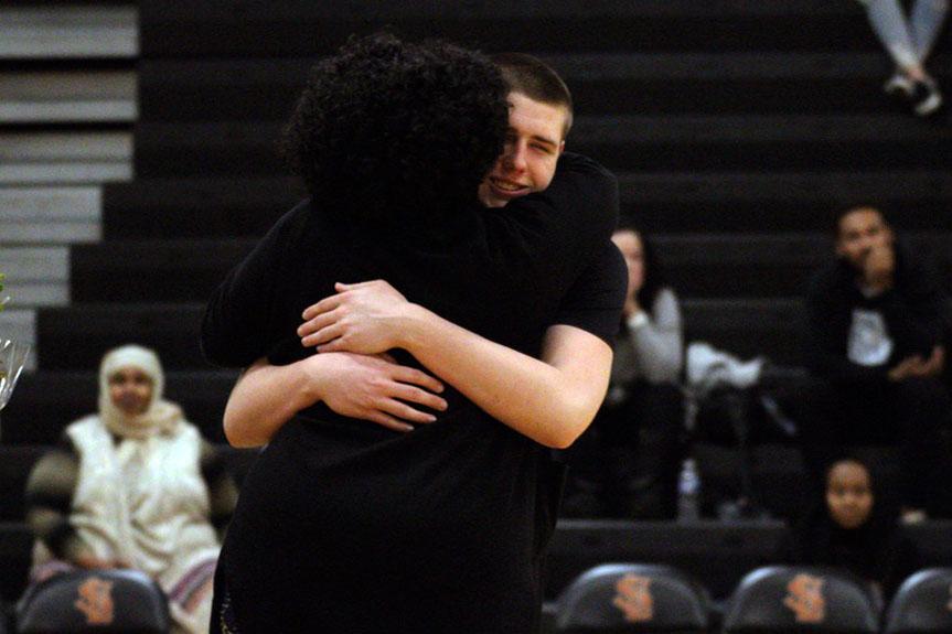 Senior Cole Ewald hugs advisor Lee-Ann Stephens during senior night before the game.