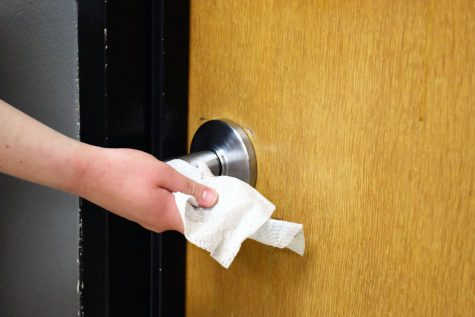 Photo illustration by Kaia Myers. A doorknob is sanitized by a disinfecting wipe. The district has cancelled all after-school events and field trips in response to COVID-19.