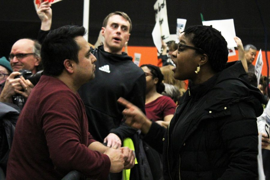 A protestor argues with a Klobuchar supporter after the cancellation announcement was made. The rally was held in the field house of the high school.