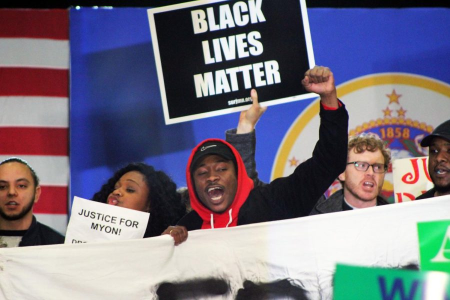 """A protestor raises his fist during a chant. Signs for the protestors included phrases such as, """"Jail killer KKKops,"""" """"Free Myon,"""" """"What's the sentence for being innocent"""" and """"Justice delayed is justice denied."""""""