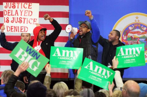 Protestors lead chants from the stage. At the beginning of the rally, the group flooded onto the stage and didn't leave until the event was cancelled.