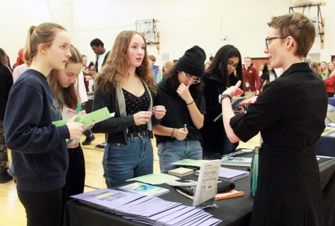 Freshmen Leila Campbell, Maren Wilsey, Cecelia Jensen, Elena Ortiz, and Alicia Narais talk with a representative from Aveda Institute Minneapolis at the college fair March 11. Students who are interested in receiving college credits as high schoolers can participate in PSEO.