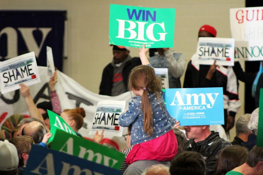 """A young girl sits on someone's shoulders and holds up a """"win big"""" sign in support of Sen. Klobuchar. Klobuchar announced she would be leaving the race March 2."""