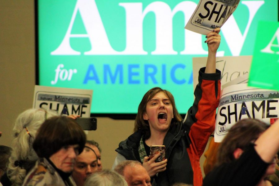 A protestor holds up a poster designed like a Minnesota license plate with the word shame. The group was there to bring attention to Myon Burrells imprisonment, a case Sen. Klobuchar prosecuted.