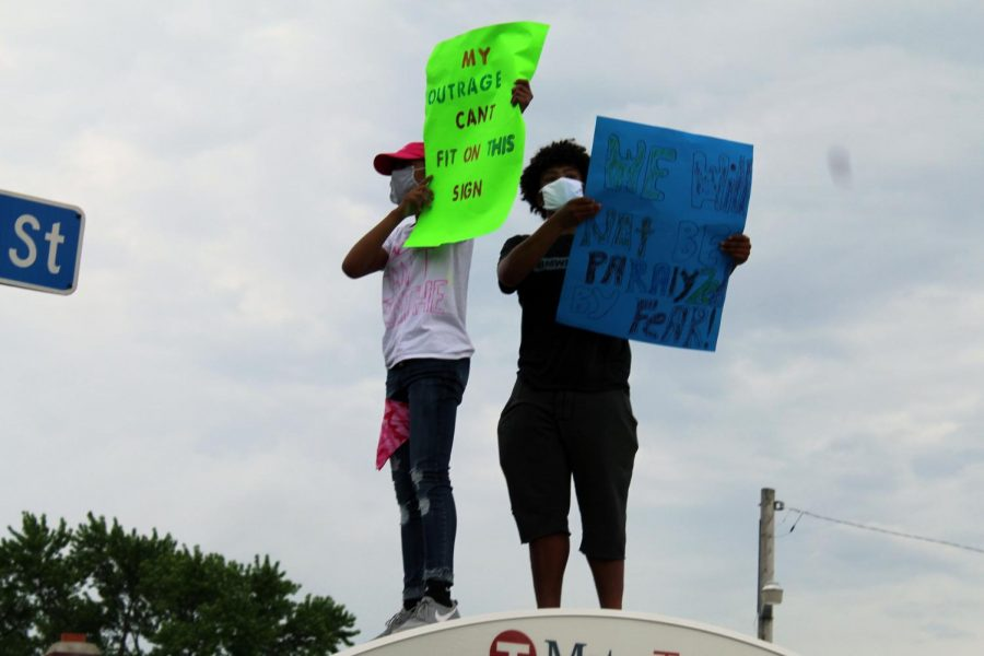 """Two protesters stand on top of a bus stop shelter holding signs that read, """"My outrage can't fit on this sign"""" and """"We will not be paralyzed by fear!"""""""