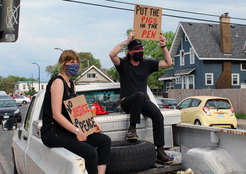Two protesters sit on top of their car holding signs for oncoming traffic. The protest began on Chicago Avenue and later marched to the 3rd Precinct.