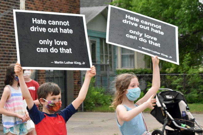 "Two children hold up signs with the qoute ""Hate cannot drive out hate, only love can do that,"" by Martin Luther King Jr."