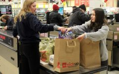 Echowan staffers and juniors Casey Hunter and Rachel Stein bag a customer's groceries Jan. 19 at Cub Foods during a Echowan fundraiser. Echowan has been attempting to raise money to buy yearbooks that they can give away to seniors who can't afford one.