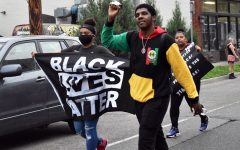 "Two protesters show strength with one carrying a ""Black Lives Matter"" flag while the other raising a fist. Following the death of George Floyd May 25, protesters gathered to honor Floyd and fight against police violence."