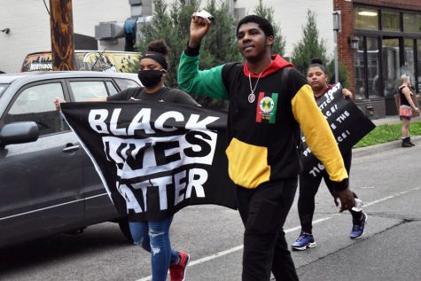 "Two protesters show strength with one carrying a ""Black Lives Matter"" flag while the other raising a fist. Following the death of George Floyd May 25, protestors gathered to honor Floyd and fight against police violence."