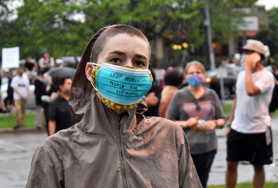 "A protester wears a mask with the saying ""stop murdering people for surviving."" Over 6,000 people attended the protest, according to the ""I Can't Breathe"" Facebook group."