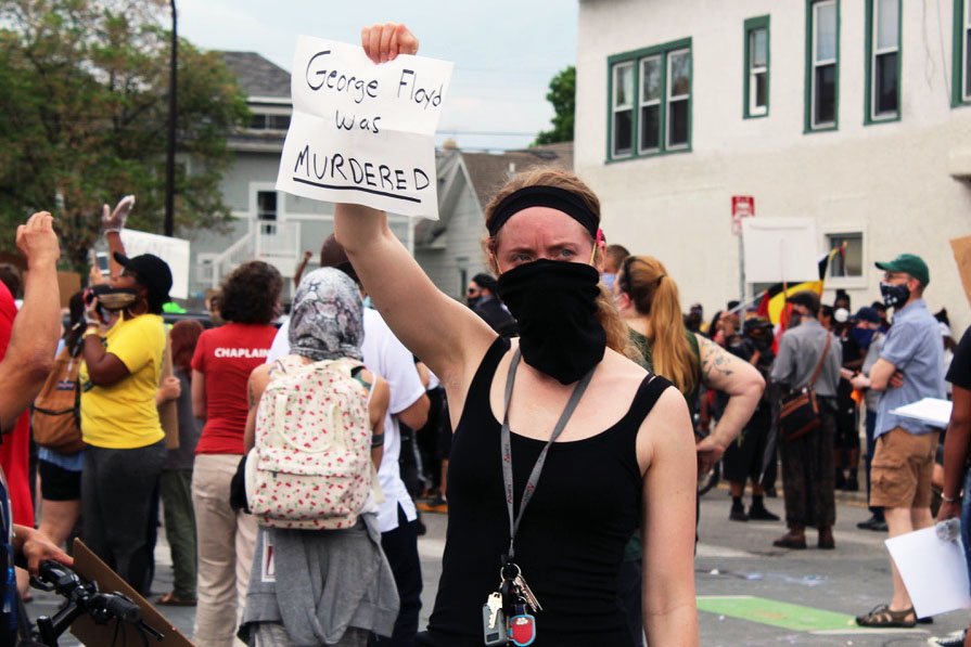"A woman takes part in a protest May 26 on Chicago Avenue, holding a sign reading, ""George Floyd was murdered."" Floyd died May 25 after being detained and choked by four Minneapolis police officers, sparking citywide protests."