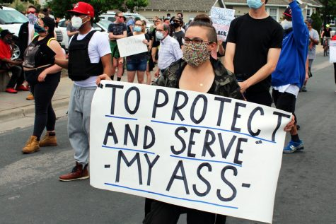 "A woman holds a sign with the words ""'To protect and serve' my ass"" during a protest on Chicago Avenue to honor George Floyd May 25. After protests turned violent, many cities and counties have implemented mandatory curfews."